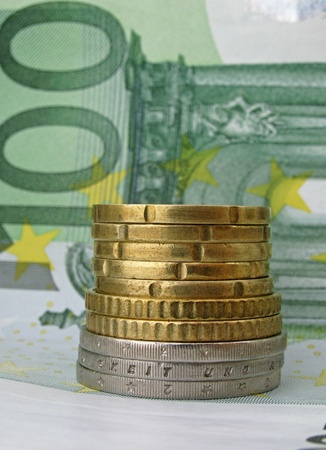 one hundred euro banknote: pile of coins on one hundred euro banknote Stock Photo
