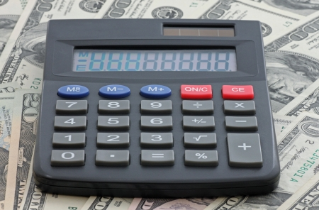 one hundred dollars: calculator on heap of one hundred dollars banknotes