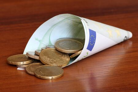 one hundred euro banknote: Euro coins in rolled one hundred euro banknote Stock Photo