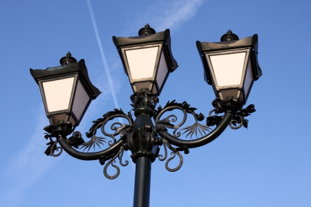 triple vintage street lamp over blue sky photo