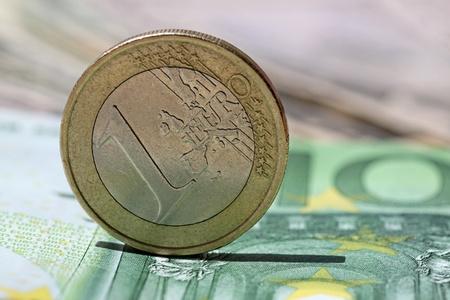 one hundred euro banknote: una moneda de euro en un billete de cien euros Foto de archivo