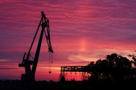 construction navale: silhouette de grue sur les plantes de la construction navale au lever du soleil