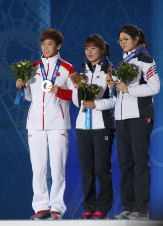 SOCHI, RUSSIA - FEBRUARY 22, 2014  Kexin Fan  CHN  Seung-Hi Park  KOR  Suk Hee Shim  KOR  during short track Ladies  1000m medal ceremony at Sochi 2014 XXII Olympic Winter Games
