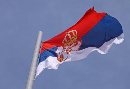 flag of Serbia over blue sky photo