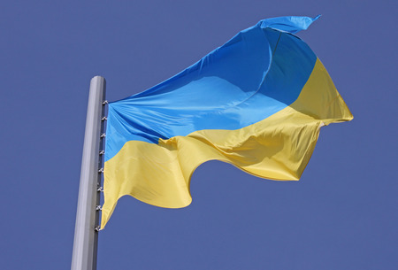 flag of Ukraine over blue sky photo