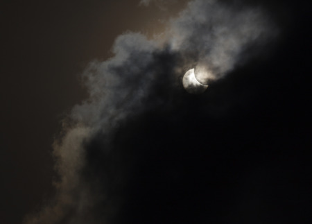 partial: view on partial solar eclipse behind clouds