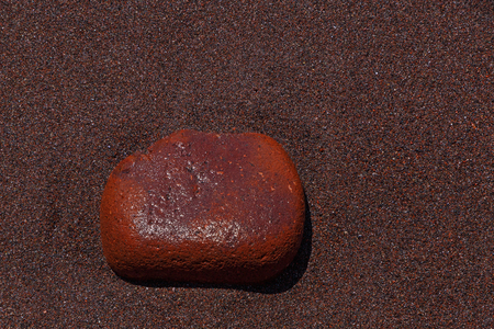 red stone: red stone on sand of Red Beach on Santorini