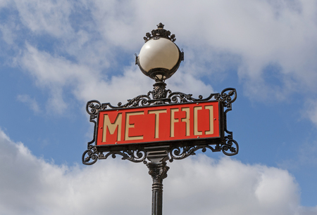 Metro sign in Paris against blue sky with clouds