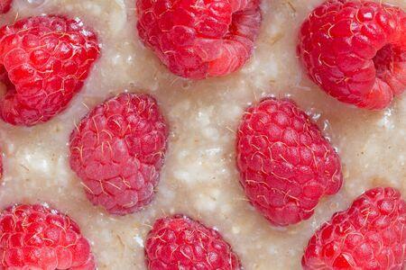 close up of oatmeal porridge with honey and raspberries