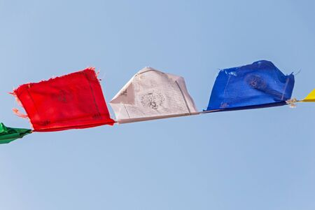 close up of Tibetian prayer flags waved against blue sky