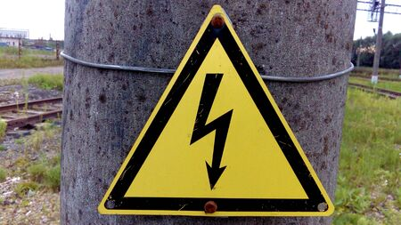 The photograph shows a sign indicating high voltage