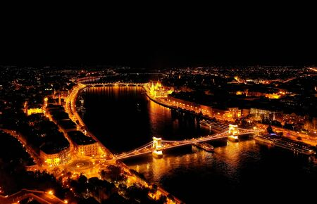 Beautiful night view of the old city of Budapest from a height, shot on a drone. In the middle of the Danube river and chain bridge. Panarama night view.