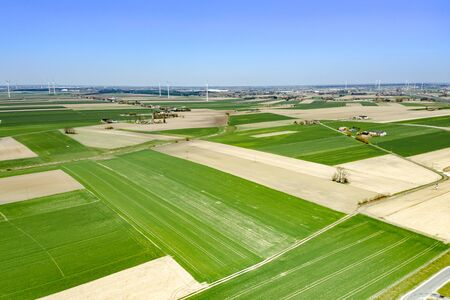 Birds Eye View of the Fields and agricultural parcels. Photo from drone. In the distance, villages and windmills. The contrast of plowed fields and fields that are already sown, green and yellow fields stretching far to the horizon, shot from above.