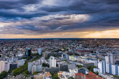 Beautiful evening sky over the German capital Belin. Taken from a bird's-eye view, from a drone. The metropolis extends as far as the horizon. Cloudy weather.