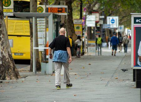 An elderly man walks on a wide sidewalk. Shot from behind.