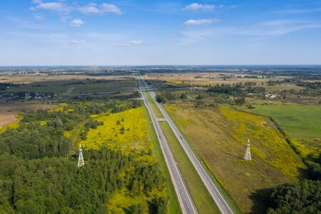 A long, straight two-lane highway that goes into the distance. On both sides is a forest and a field. Taken from a height on a drone.