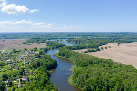 Beautiful view of the winding river going into the distance. The river flows through the forest. A small village is visible on the left Bank. Shot on a drone from a height.