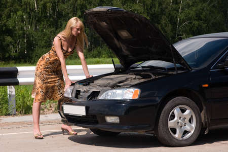 Young woman looks under a cowl of the car  photo
