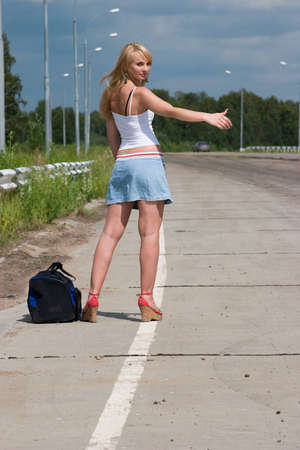 Young woman stopping a car on the road  photo