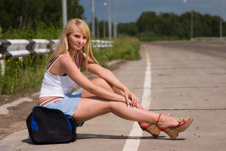 flank: The girl, travelling  hitch-hiking, sits on a flank