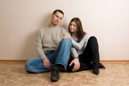 Young man and woman sit near wall in empty room.