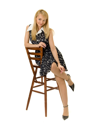 Pretty girl sitting on high wooden chair.