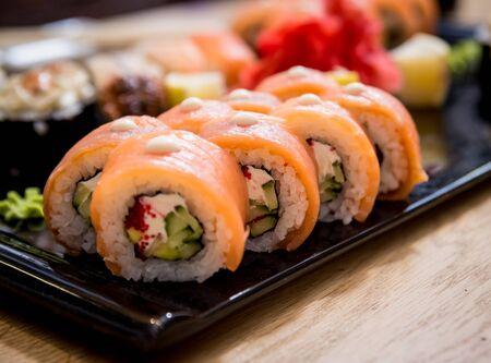 Ensemble de sushis. Rouleaux de saumon, d'anguille et de caviar rouge sur une assiette en bois. Le restaurant.