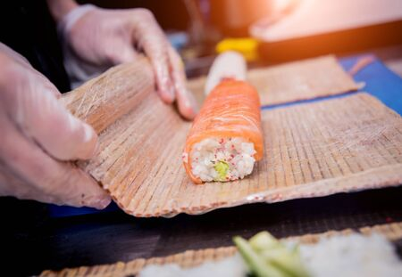 Process of making sushi and rolls at restaurant kitchen. Chefs hands with knife.