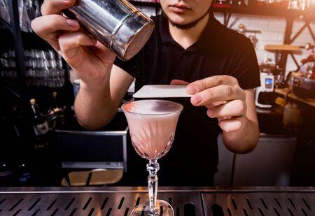 Bartender is making cocktail at bar counter. Fresh cocktails. Barman at work. Restaurant. Nightlife.
