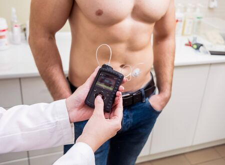 The doctor connects an insulin pump to a patient with diabetes