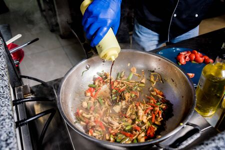 Chef cooking pasta with vegetables in pan. Italian style cuisine. Restaurant.
