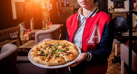Waiter, carrying dish with tasty pizza with chicken and vegetables. Restaurant. Stok Fotoğraf