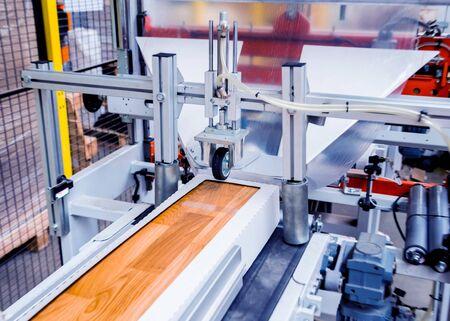 Linea di produzione della fabbrica di pavimenti in legno. Macchina automatica per la lavorazione del legno CNC. Background industriale