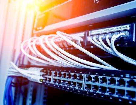 Conmutador de red y cables ethernet en colores rojo y blanco. Centro de datos