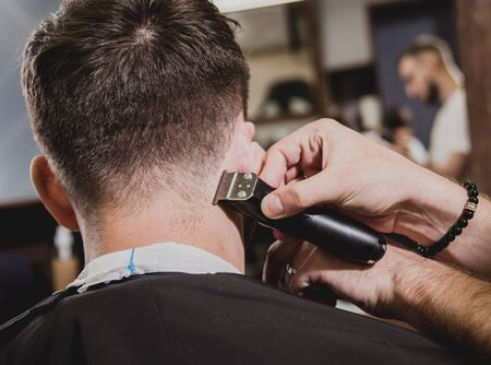 Young man with trendy haircut at barber shop. Barber does the hairstyle and beard trim. Concept barbershop.
