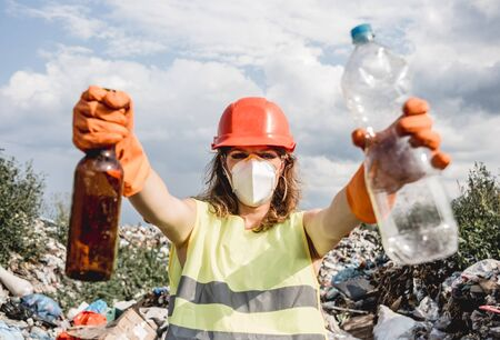 Woman volunteer helps clean the field of plastic garbage. Bushes and sky in the background. Earth day and ecology. Concept