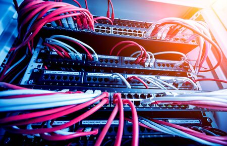 Network switch and ethernet cables in red and white colors. Data Center