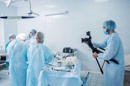 El camarógrafo dispara al cirujano y a los asistentes en el quirófano con equipo quirúrgico. Antecedentes medicos