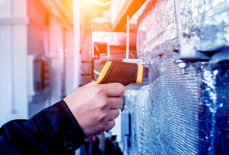 Technician use infrared thermal imaging camera to check temperature at fuse-box. Modern equipment
