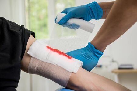Nurse dressing wound for patient's hand with deep skin cutting. Medical background