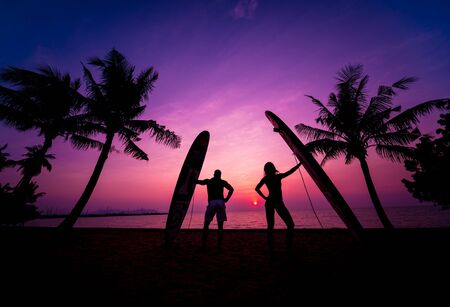 Silhouette of surfers couple holding long surf boards at sunset Standard-Bild - 139940629