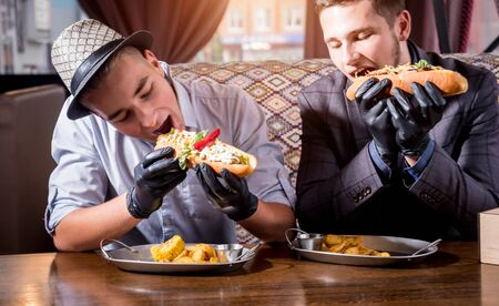Two hungry young men eating a hot dogs in cafe. Restaurant