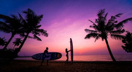 Silhouette of surfers couple holding long surf boards at sunset Standard-Bild - 139980843