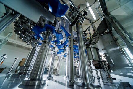 Automatic filling machine pours water into plastic PET bottles. Imagens