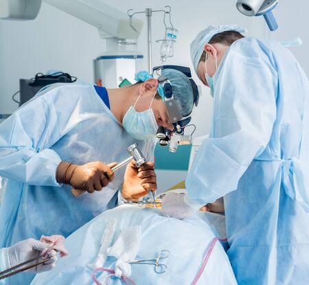 Cirugía de la columna. Grupo de cirujanos en quirófano con equipo quirúrgico. Foto de archivo