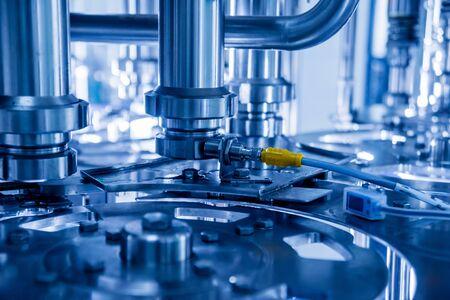Automatische vulmachine giet water in plastic PET-flessen. Productie van brouwen. Industriële achtergrond. Stockfoto