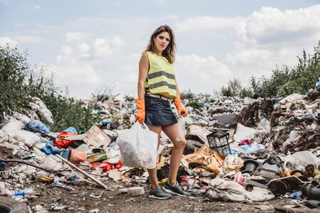 Woman volunteer helps clean the field of plastic garbage.