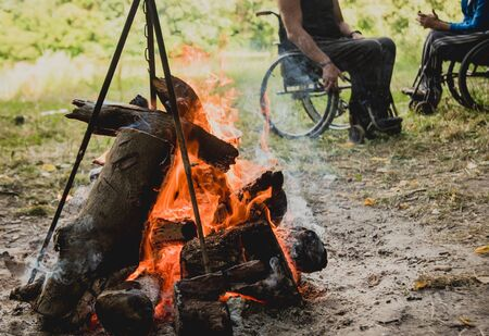 Disabled man resting in a campsite with friends. Wheelchair in the forest