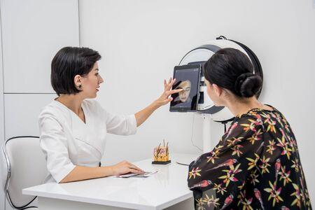 Face skin analyze system. Cosmetologist analyzing woman face. 스톡 콘텐츠