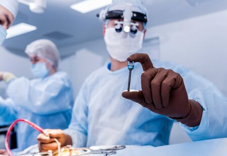 Spinal surgery. Surgeon show polyaxial screw in operating room
